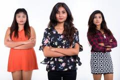 Le studio a tiré de trois jeunes amies persanes de femme avec la croix de bras Images stock