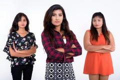 Le studio a tiré de trois jeunes amis persans de femme se tenant avec a Photographie stock libre de droits