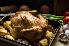 Le style de CCountry a rôti le poulet sur la table de cuisine en bois, oignons, oignons blancs, pommes de terre, pommes, dîner de Photo stock