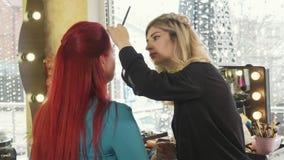 Le styliste de maquillage fait de beaux sourcils à la jeune femme rousse à la boutique de beauté banque de vidéos