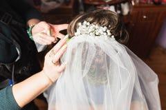 Le styliste en coiffure fait la jeune mariée avec de beaux hairdress élevés de cheveux blonds au salon image stock