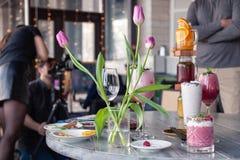 Le styliste et le photographe de nourriture d?corent, pr?parant pour tirer de divers cocktails, milkshakes, les smoothies, vase ? photos libres de droits