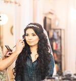 Le styliste fait la jeune mariée de maquillage le jour du mariage photographie stock