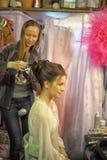 Le styliste fait le modèle de cheveux Photographie stock