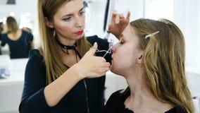 Le styliste forme des cils utilisant le bigoudi pour la jeune fille clips vidéos