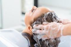 Le styliste lave des cheveux de clients photographie stock
