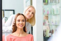 Le styliste montre la coiffure à son client photos stock