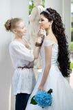 Le styliste prend soin de la mariée Image libre de droits