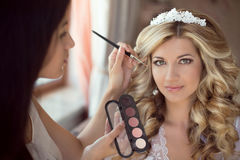Le styliste professionnel fait la jeune mariée de maquillage le jour du mariage beau Photographie stock libre de droits