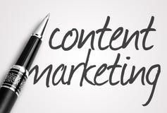 Le stylo écrit le marketing satisfait sur le papier Images libres de droits