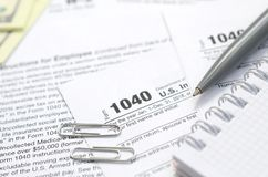 Le stylo, le carnet et les billets d'un dollar est des mensonges sur la feuille d'impôt 1040 Photo libre de droits