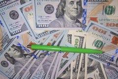 le stylo de boule d'un vert tsven dans la perspective des dollars d'argent, euro finances d'affaires photographie stock libre de droits