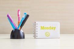 Le stylo de couleur de plan rapproché avec le bureau en céramique noir rangé pour le stylo et le mot de lundi de jaune dans l'émo Photographie stock libre de droits
