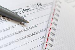 Le stylo et le carnet est des mensonges sur la feuille d'impôt U 1040 S Individua Photographie stock libre de droits