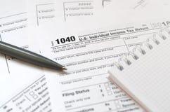 Le stylo et le carnet est des mensonges sur la feuille d'impôt U 1040 S Individua Images libres de droits