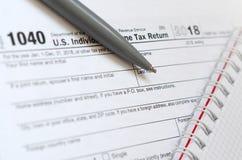 Le stylo et le carnet est des mensonges sur la feuille d'impôt U 1040 S Individua Photo stock