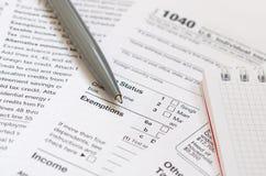 Le stylo et le carnet est des mensonges sur la feuille d'impôt U 1040 S Individua Photos libres de droits