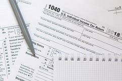 Le stylo et le carnet est des mensonges sur la feuille d'impôt U 1040 S Individua Image libre de droits