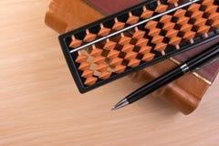 Le stylo et l'abaque au-dessus du vieux vintage réservent pour avec l'espace de copie sur la table en bois Photo stock