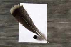 Le stylo et le papier nostalgiques de plume d'oiseau Photos stock