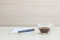 Le stylo noir de plan rapproché sur le livre blanc avec du café noir dans la tasse de café transparente sur le bureau et le mur e Photos stock