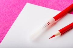 Le stylo rouge de crayon et de feutre de rouge sur le livre blanc couvrent papeterie Images libres de droits