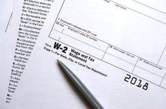 Le stylo se trouve sur la déclaration de salaire et d'impôts de la feuille d'impôt W-2 Le Tim image libre de droits