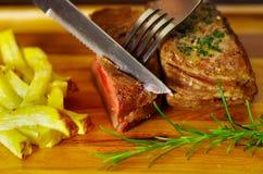 Le succulent délicieux a grillé la viande sur la table en bois utilisant des ustensiles de cuisine Image libre de droits