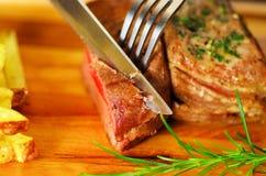 Le succulent délicieux a grillé la viande sur la table en bois utilisant des ustensiles de cuisine Photos stock