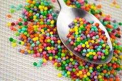 Le sucre coloré arrose dans la cuillère Photo libre de droits