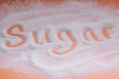 Le sucre de mot écrit dans des grains de sucre Vue supplémentaire photos stock