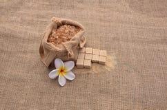 Le sucre et le Plumeria fleurissent sur le fond de toile à sac de chanvre Photo stock