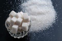 Le sucre granulé et le sucre raffiné de blanc sur la table noire apprêtent photo stock