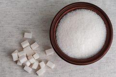 Le sucre raffiné et le bol blancs de sucre granulé, se ferment vers le haut du principal v photos stock
