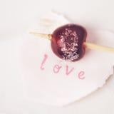 Le sucre rouge de cerise a enduit sur un bâton de l'amour de mot Images stock