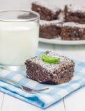 Le sucre a saupoudré les 'brownie' faits maison avec le verre de lait image libre de droits