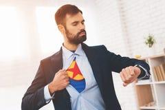 Le super héros caché mène une double vie Il est dans un costume, mais sous lui des mensonges les vêtements d'un super héros Image libre de droits