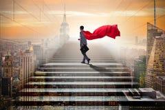 Le super héros d'homme d'affaires réussi dans le concept d'échelle de carrière Photo stock