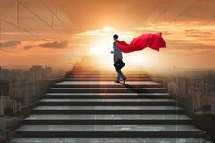 Le super héros d'homme d'affaires réussi dans le concept d'échelle de carrière photographie stock libre de droits