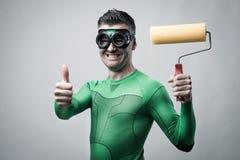 Le super héros drôle avec le rouleau de peinture manie maladroitement  Photographie stock