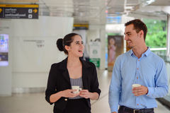 Le support d'homme d'affaires et de femme d'affaires et rire, parlent des affaires avec la tasse en plastique en main Images libres de droits