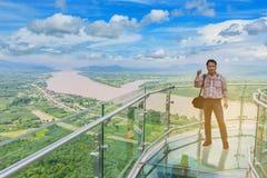Le support d'homme au skywalk thaïlandais, au beau ciel et au nuage chez le Mekong, frontière internationale entre Nong Khai Prov Image libre de droits