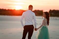 Le support de jeunes mariés dans le désert au coucher du soleil, mains de prise et regardent a Image stock