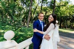 Le support de jeunes mariés sur les escaliers en parc Le jeune marié embrasse la jeune mariée Couples de mariage dans l'amour au  Photographie stock libre de droits