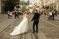 Le support de marié et de jeune mariée a fatigué sur la vieille rue illuminée par images stock