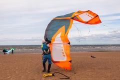 Le surfer de cerf-volant utilisant un wetsuit prépare son cerf-volant sur un d venteux Image libre de droits