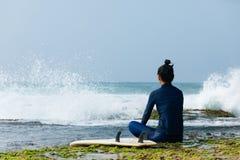Le surfer de femme s'asseyent sur le récif image libre de droits