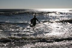 Le surfer marche dans l'eau dedans Photographie stock libre de droits