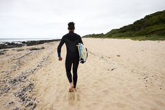 Le surfer marche le long de la plage photos stock