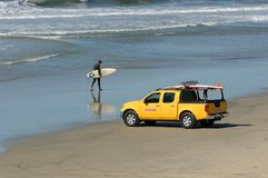 Le surfer marche plage Photographie stock